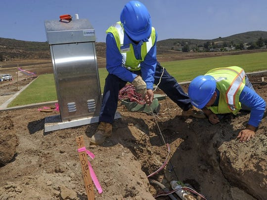 ROB VARELA/THE STAR Herlindo Mendes (left) and Raull Gonzalez work on the irrigation system for the Rams practice field on the campus of CLU in Thousand Oaks.