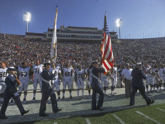 ROB VARELA/THE STAR Rams players stand on the sideline as the color guard enters the stadium before the start of Saturday night's preseason game against the Cowboys at the Los Angeles Memorial Coliseum.