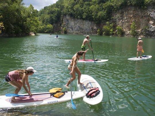 Incoming University of Tennessee freshman Carly Eakin of Bartlett, Tenn., center, slips from a paddle board into Mead's Quarry Lake during an Ignite Knox outing Tuesday, Aug. 9, 2016, at Ijams Nature Center. With Eakin are fellow freshmen Bailey Hicks of Lebanon, Tenn., left, Brennan Hughes of Medina, Tenn., and Chase Edwards of Charlotte, N.C. UT officials say that the incoming freshmen class is the largest in at least 30 years.