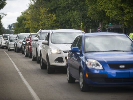 Cars line up on Andy Holt Avenue, waiting to be directed, at University of Tennessee on move-in day Saturday, Aug. 13, 2016.