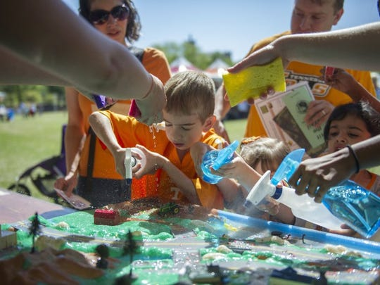 Patrick Houston, 7, of Knoxville, helps simulate a rainstorm washing pollution into Knoxville's waterways at EarthFest in World's Fair Park in downtown Knoxville on Saturday, April 16, 2016.