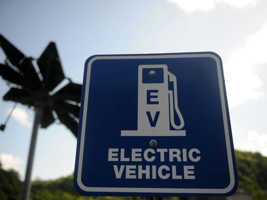 "A sign designates an electric vehicle charging station at Melton Hill Campground outside Lenoir City. Behind the sign is a ""solar flare,"" which has solar panel leafs that tilt to accommodate the angle of the sun for maximum energy production."
