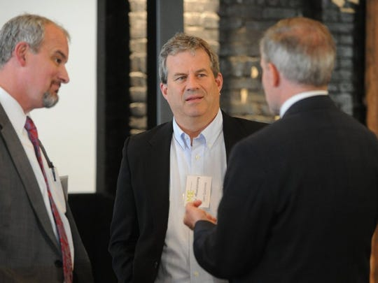"""Journalist Sam Quinones, center, speaks to Tommy Farmer, left, and Bill Dunn, both attendees of a Metro Drug Coalition dinner at The Jackson Terminal in May 2016. Quinones is the author of """"Dreamland: The True Tale of America's Opiate Epidemic."""""""