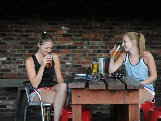 Emily Longaker, left, laughs with her friend Kaylan Powers on June 7, 2016, at the Bearden Beer Market.