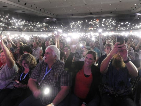 Audience members activate the flashlights on their smartphones and hold them overhead during a 2016 Beach Boys concert at the Taylor County Coliseum.