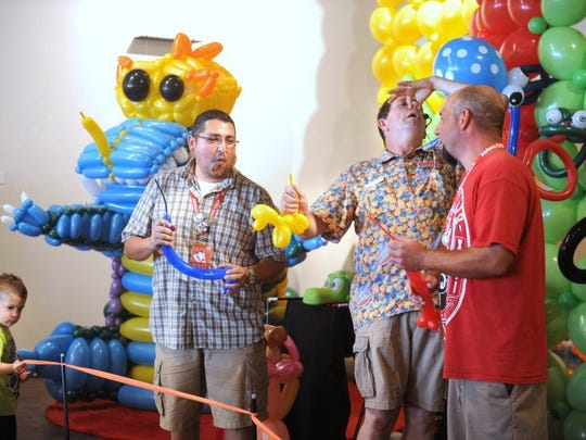 Balloon artist David McCullough (center), also known by his clown name, Korn Pop, performs with the help of audience members during the 2016 Children's Art & Literacy Festival.