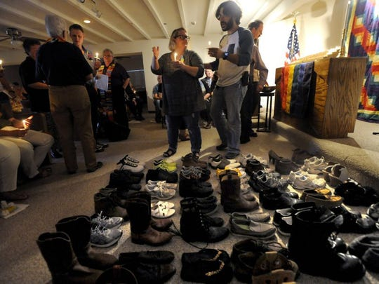 Mourners file past 49 pairs of shoes to light candles on the altar at Exodus Metropolitan Community Church after the Pulse nightclub shooting in Florida. Each pair of shoes represents one of the victims.