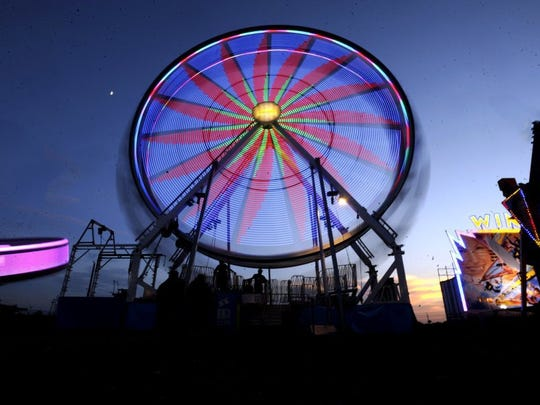 The Ferris wheel spins as the sun sets over the midway