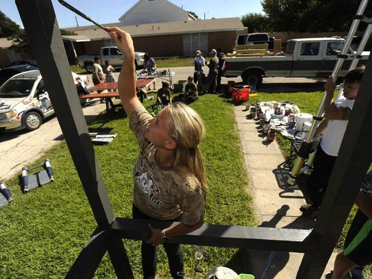 Dyess We Care Team member Gabby Baker paints the porch of a home on Beech Street in October 2016.