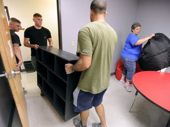 Volunteers move new furniture into one of the visitation rooms at the CPS building.