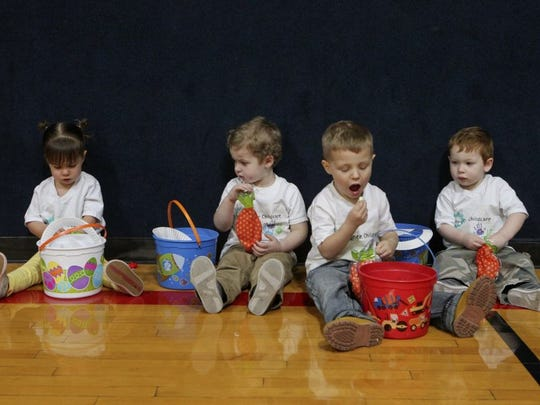 Greg Barnette/Record Searchlight Eloise Burgess, 2 , from left, Remington Williams, 3, Shawn Steyskal, 3, and Mason Williams, 1, check out their their baskets Wednesday during the YMCA's annual Egg Extravaganza n Redding.