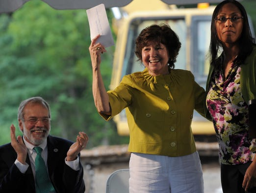 Columbia State Community College President Janet Smith holds up a check donated by Denise Carothers, president of the Rotary Club of Franklin at Breakfast, as Chancellor John Morgan claps at the groundbreaking ceremony for the new Williamson County campus Friday, July 18, 2014, in Franklin.