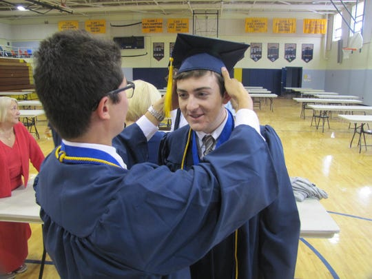 Notre Dame High School graduate Michael Hitchcock of Elmira has his cap adjusted by a classmate prior to the school's 60th commencement on Friday night.