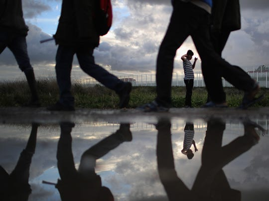 Migrants walk through the muddy grounds of the Jungle