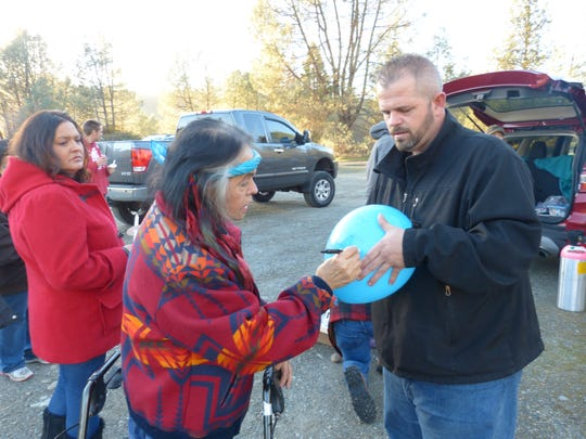 Stacey Smart's mother, Paula (center), writes a message on one of the balloons honoring her daughter's 52nd birthday. Also pictured are Smart's son-in-law, Mike Hamann, and her sister, Melissa.