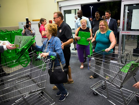 Shoppers grab carts as employees hand out reusable