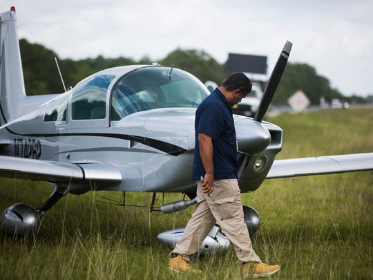 Juan Garcia, an aviation safety inspector with the Federal Aviation Administration, checks a 1975 Grumman AA-5 Bravo on the side of I-75 between mile markers 54 and 50 after an unexpected landing Monday, June 12, 2017, in Collier County. The pilot was headed to Okeechobee but landed the plane due to power loss.