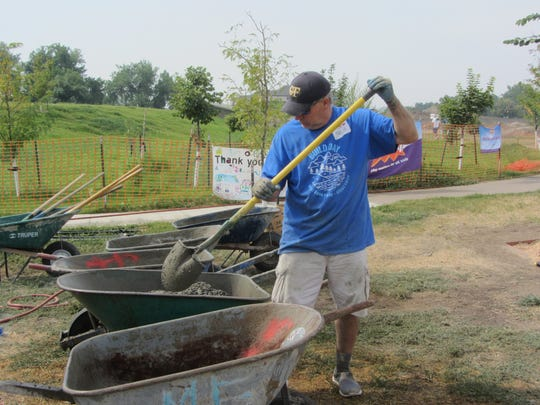 Ted Stuff mixes cement Saturday morning at West Bank Park. He was among 200 volunteers who built a playground at the park.