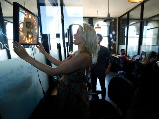 Pamela Fox chief technology officer with Woebot, hangs a picture frame that contains the logo for the start-up as others work in San Francisco on July 28, 2017.  Woebot primarily consists of psychologists and academics that has created a chatbot that offers users cognitive behavioral therapy. The bot is named Woebot, and users chat with it each day to get in touch with their own feelings and emotions, and do exercises that help alleviate stress, anxiety, depression.  (Genaro Molina/Los Angeles Times/TNS)