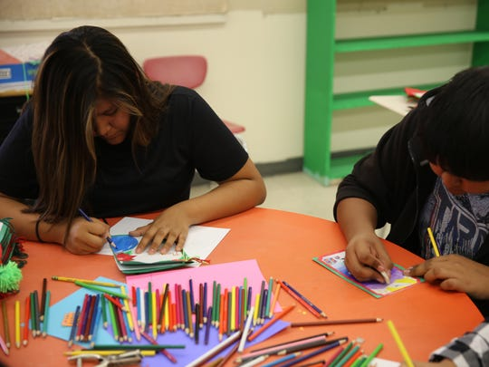 Newcomb Middle School eighth-graders Katie Tsosie, left, and Albert Lapahie work on their cards during art class on Wednesday.