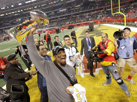Packers cornerback Charles Woodson is able to lift the Lombardi Trophy despite a broken collarbone.