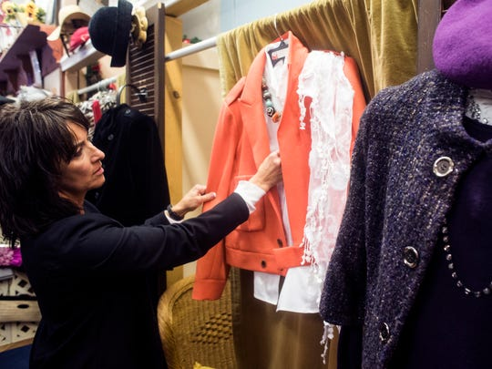 """Angie Seabury arranges two of her favorite blazers with tops and accessories in her shop, A Time or Two, on Central Avenue. """"I love the cut and the textures are awesome,"""" she said """"I love the layering."""""""