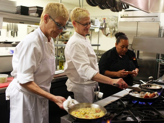 Co-owners of IM Tapas Isabel Pozo Polo, left, and Mary Shipman, center, prepare dishes for customers of their Naples restaurant in April 2014.