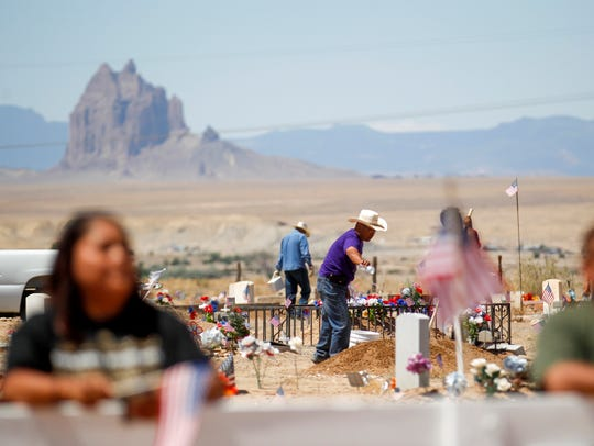 Community members tend to the graves of their loved ones on Monday at the Shiprock Veterans Memorial Cemetery.