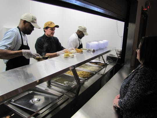 CHEER staff members serve the traditional chicken dinner
