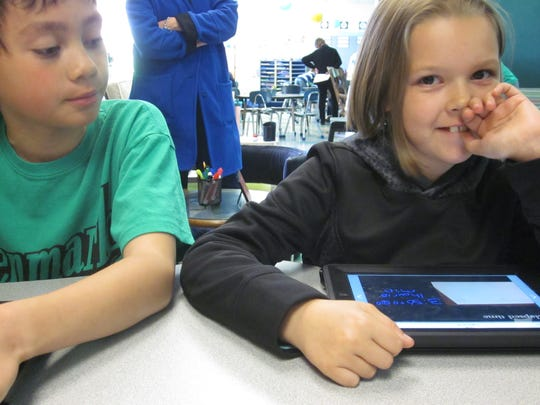 Nine-year-olds Parker Welch (right) and Sam Reimann show off programs and projects on their iPads at Washington Elementary School in Merrill on Thursday. The two are in a third-grade pilot program and use the devices in class with teacher Terri Eckes.