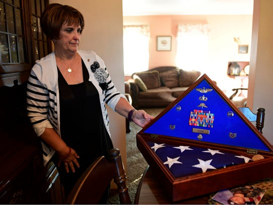 Sue Zerbe stands next to a box with a flag and medals