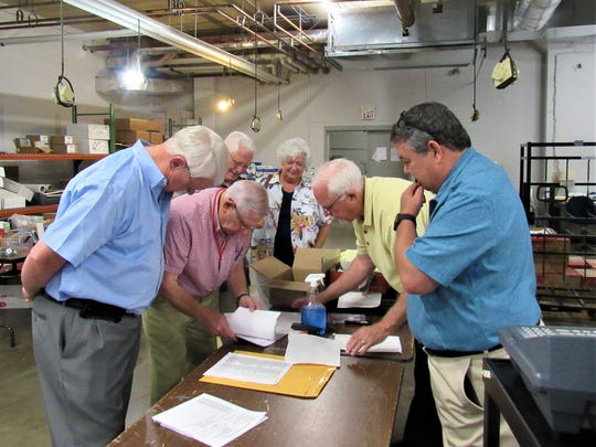Participants look over sample paper ballots that will