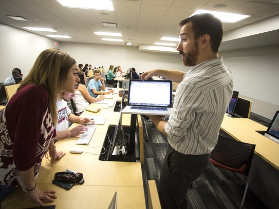 Dayne Logan, right, works with students at Grand View