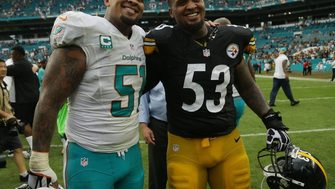 Miami Dolphins center Mike Pouncey (51) and brother Pittsburgh Steelers center Maurkice Pouncey (53) greet each other at the end an NFL football game, Sunday, Oct. 16, 2016, in Miami Gardens, Fla. (AP Photo/Lynne Sladky)