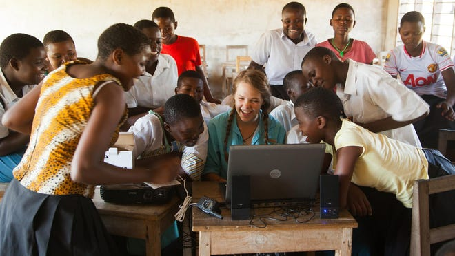 Chocolate University student Kelsey Esther shows students at Mwaya Secondary School, near Tenende, Tanzania, how to use a computer.