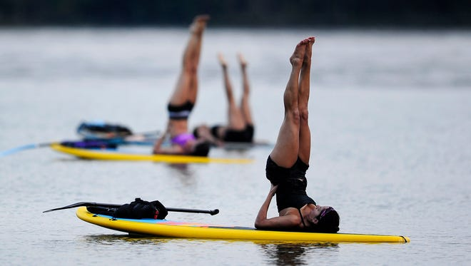 A Nashville Paddle Co. yoga class does poses on Percy Priest Lake as they float on paddleboards.