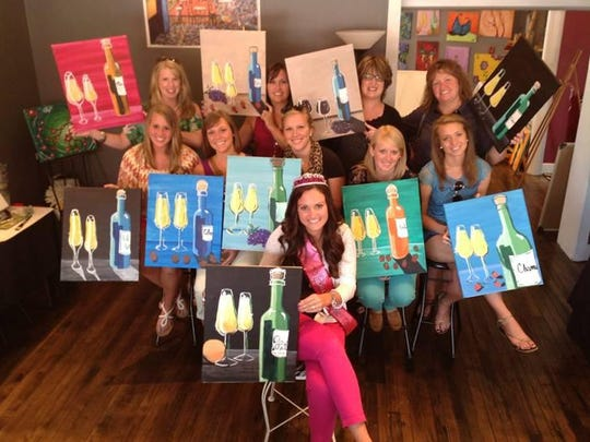 Guests show off their artwork at a Mimosa and a Masterpiece class.