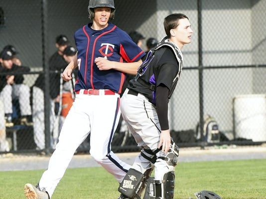 Chambersburg's Hunter Brindle, left, scores a run against Mifflin County during the second game of a doubleheader on Tuesday. The Trojans won, 8-7 in nine innings.