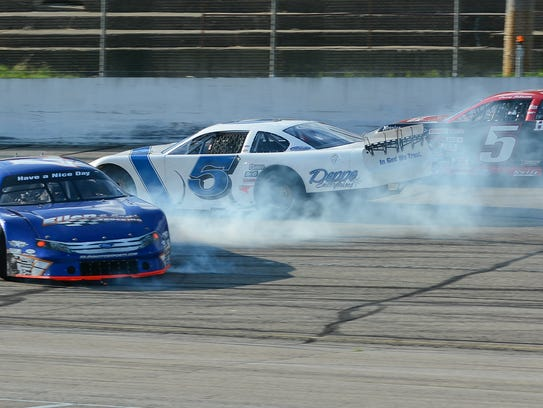 Johnny Sauter (white car) and Casey Johnson drive past Jonathan Eilen after Sauter spun Eilen with 16 laps to go as they battled for second place in the Joe Shear Classic on May 6 at Madison International Speewday.