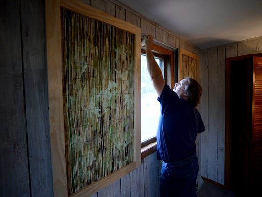 Dennis Clark hangs window blinds in a bedroom with an outdoors theme as part of Special Spaces' dream bedroom makeover for siblings Evan and Becca Connelly at the family's home in De Pere on Saturday.