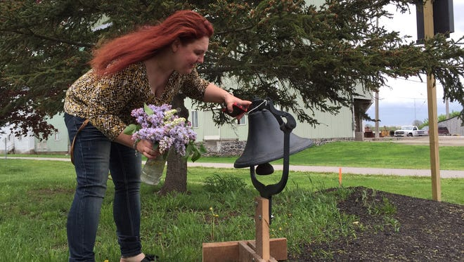 Jennifer Millsap, mother of April Millsap, places a vase of flowers near a bell at the future site of a memorial garden in honor of April Millsap.