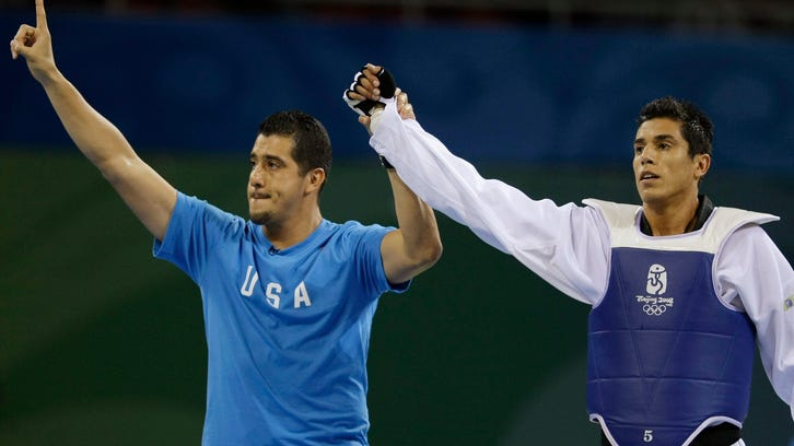 FILE - This Aug. 22, 2008, file photo shows Steven Lopez, right, celebrating with his brother and coach Jean after defeating Azerbaijan's Rashad Ahmadov in a bronze medal match for the men's taekwondo -80 kilogram class at the Beijing 2008 Olympics in Beijing. Two-time Olympic champion Steven Lopez complained to the U.S. Olympic Committee that he was subject to an ``institutionalized witch hunt'' designed to undermine his success _ a piece of Congressional testimony offered by USA Taekwondo to undercut the notion that the organization was unwilling to discipline its top athletes for sex-abuse and other cases. Lopez is currently under suspension while the U.S. Center for SafeSport investigates a case against him. His brother and coach, Jean, has been permanently banned for sexual misconduct. (AP Photo/Matt Dunham, File)
