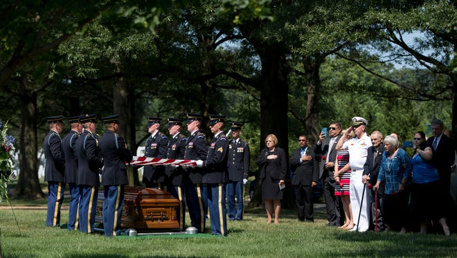 The flag is lifted from the casket of U.S. Army Air Force 2nd Lt. Stephen Biezis by members of the Army's 3rd U.S. Infantry Regiment, or The Old Guard, during a burial service at Arlington National Cemetery in Arlington, Va., Friday, Aug. 14, 2015. Biezis was a missing service member from World War II.