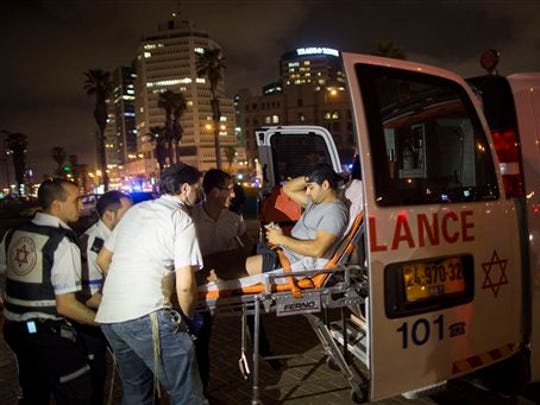 A wounded man is evacuated from the scene of a stabbing attack in Jaffa, a mixed Jewish-Arab part of Tel Aviv, Israel, on Tuesday, March 8, 2016.