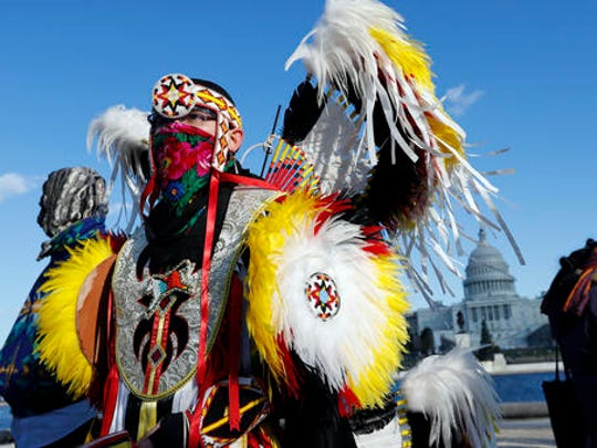 Max Yamame, from San Antonio, Texas, is dressed to perform a dance on Capitol Hill in Washington, Saturday, Dec. 10, 2016, during a demonstration to protest the Dakota Access oil pipeline. A federal court battle over whether the developer of the pipeline can finish the $3.8 billion project will linger at least into the first couple months of the new year.