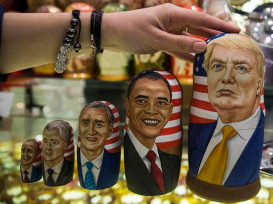 FILE - In this Tuesday, Nov. 8, 2016 file photo, traditional Russian wooden nesting dolls called Matreska depicting U.S. presidents, from left, George H.W. Bush, Bill Clinton, George W. Bush, Barack Obama and U.S. presidential candidate Donald Trump, are displayed in a shop in Moscow, Russia. Hacked emails, disclosed by WikiLeaks, revealed at-times embarrassing details from Democratic Party operatives in run-up to Election Day, leading to the resignation of Democratic National Committee chair Debbie Wasserman Schultz and other DNC officials. The CIA later concluded that Russia was behind the DNC hacking in a bid to boost Donald Trump's chances of beating Hillary Clinton.