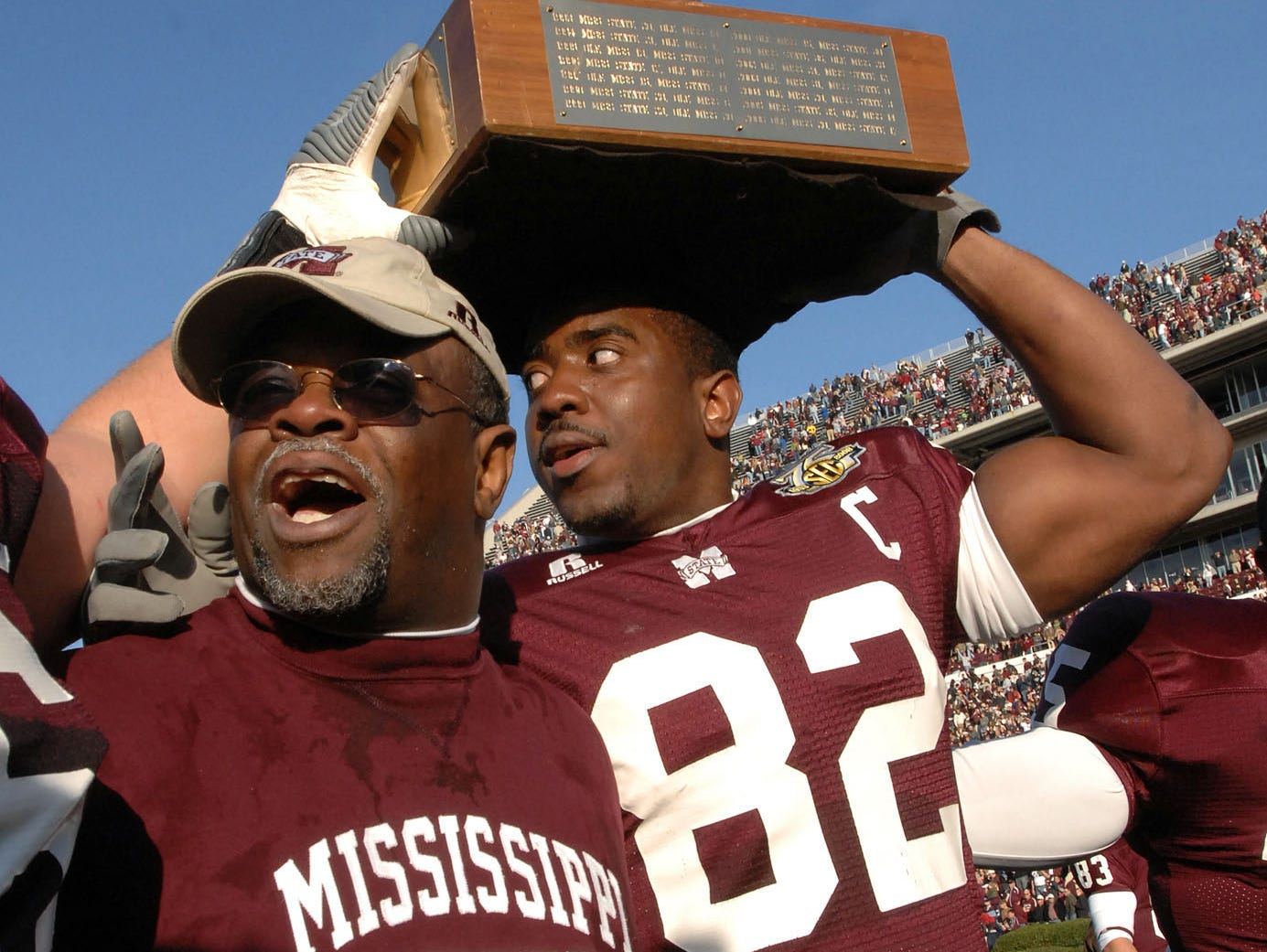Mississippi State Coach Sylvester Croom and TE Jason Husband celebrate State's win with the Egg Bowl Trophy in 2007.