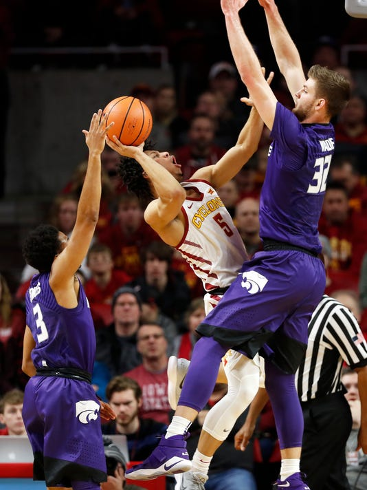 Iowa State guard Lindell Wigginton (5) drives to the basket between Kansas State's Kamau Stokes, left, and Dean Wade, right, during the first half of an NCAA college basketball game, Friday, Dec. 29, 2017, in Ames, Iowa. (AP Photo/Charlie Neibergall)