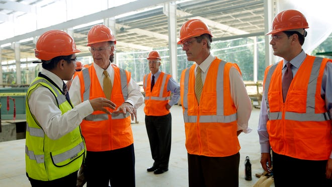 Gov. Robert Bentley talks with Golden Dragon USA President Roger Zhang, left, during an August 29, 2013, tour of the Alabama plant as it was under construction near Pine Hill.