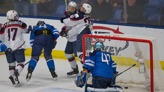 Team USA's Kendall Coyne (right) congratulates goal-scorer Hilary Knight. At left is Jocelyne Lamoureux.